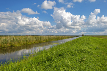 Clouds over a canal through a rural landscape