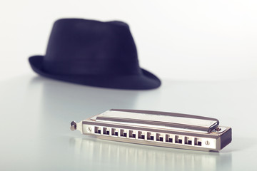 Hat and harmonica on white background