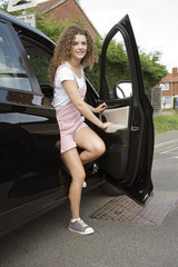Young female car driver getting out of the drivers seat