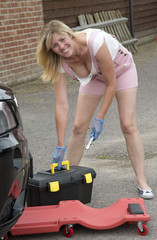 Woman carrying out maintenace on her car