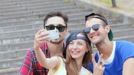 Cheerful girl sitting on the steps of his friends makes selfie