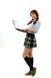 School girl wearing plaid uniform and holding a laptop