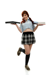 School girl holding books in one hand and a laptop in the other