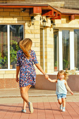 Mother and daughter walking in city park