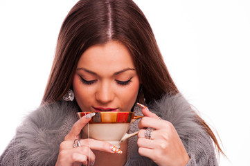 Young brunette drinking hot tea - isolated on white