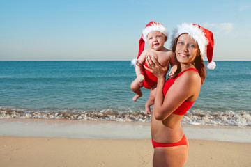woman and baby in santa hat on sea