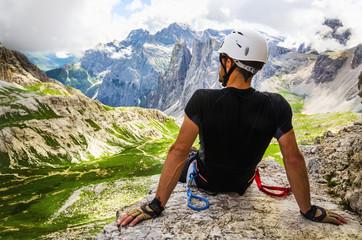 Climber on via ferrata Torre di Toblin, resting on the top