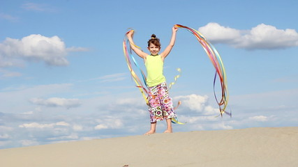 happy little girl waving with colorful ribbons on windy beach