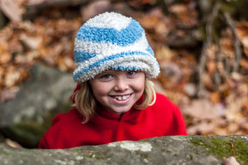 Young girl wearing hat smiles up at camera
