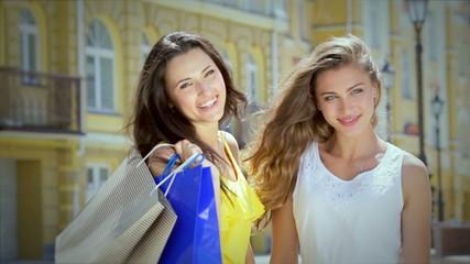 Two girls pleasing cuddling holding shopping bags