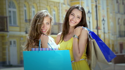 Two girls pleasing and posing while holding shopping bags with