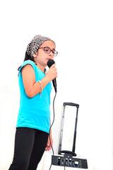 Little cute brunette girl singing karaoke