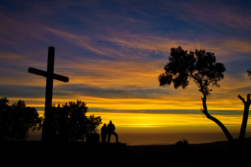 Couple viewing the sunset under a cross