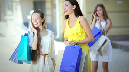 Two young pretty girls happy new purchases on the background of