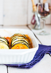 hot ratatouille in a baking dish on a white background, vertical