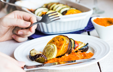 processes food vegetable ratatouille with a fork and knife, hand