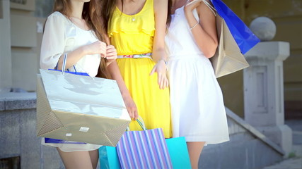 Three young cute girls happily discussing new purchases on a sun