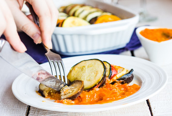 eat vegetable ratatouille with a fork and knife, hands