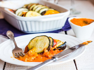 juicy ratatouille served in a round plate with sauce, fork, knif