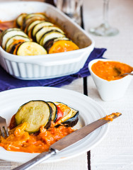 vegetable ratatouille in a round plate with sauce, knife, vertic
