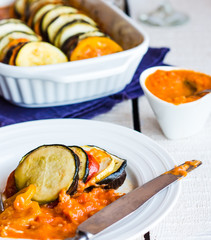 vegetable ratatouille in a round plate with sauce, knife, closeu