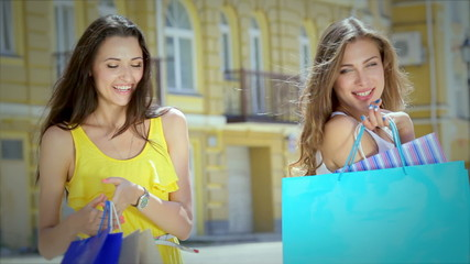 Two young glamorous girls go hand in hand with shopping bags