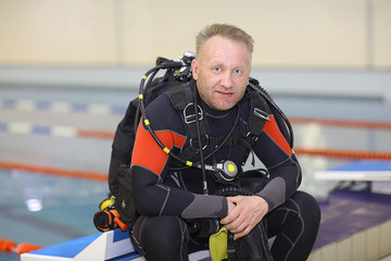 man in a diving suit on the bank pool