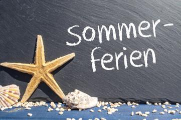Schiefertafel mit Seestern und Muscheln und Sommerferien