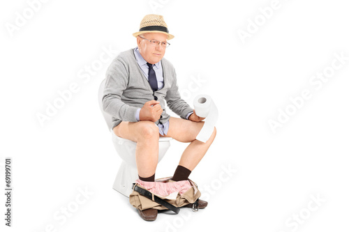 Senior man pushing hard seated on a toilet