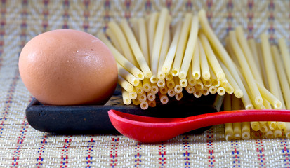 Egg with spaghetti on a wood with red plastic spoon