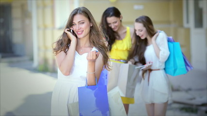 Girl talking on the phone on the background of a shopaholic girl