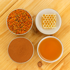 Honey, honeycomb, pollen and cinnamon in bowls