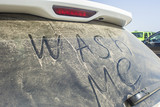 Dirty rear window of the car and inscription Wash me