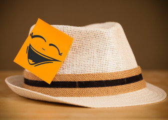 Post-it note with smiley face sticked on hat