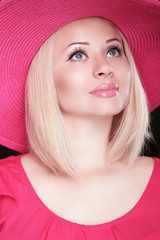 Beautiful blond woman with makeup, smiling girl posing in pink h