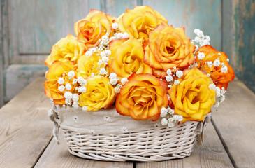 Bouquet of orange roses in a white wicker basket