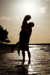 Silhouette of a young couple at sunset near the shore of the oce