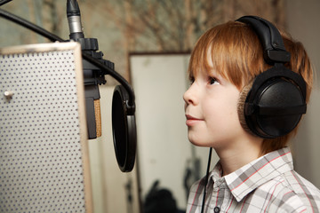 redhead boy standing in front of a microphone with headphones