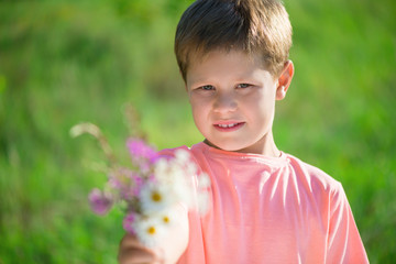 Cut little boy with bunch of flowers