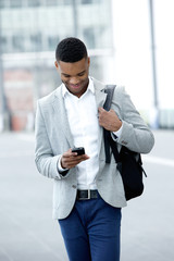 Young man walking and looking at mobile phone