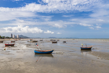 fishing boats on the beach mud on blue sky background