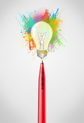 Pen close-up with colored paint splashes and lightbulb