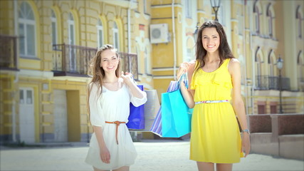 Two cheerful girls walking boutiques back to us then turn around