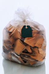 paper in clear plastic garbage bag with tag