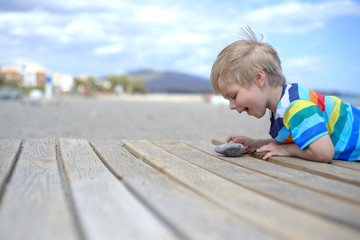 Boy playing on a wooden walkway on the beach