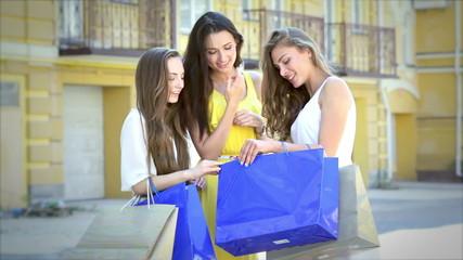 Three cute girls meet while shopping, and consider buying fashio