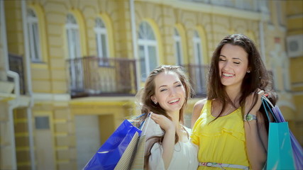 Two graceful cute girl posing with trendy shopping while shoppin