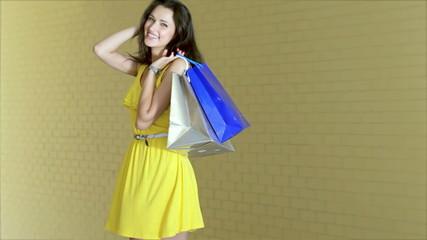 Graceful beautiful girl posing with trendy shopping while shoppi