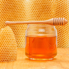 Honey in jar with dipper on honeycomb background