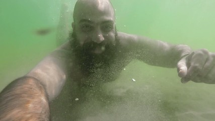 bearded man underwater in summertime